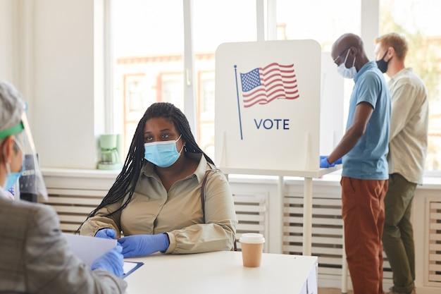 Multi-etnische groep mensen die maskers dragen die bij stembureau stemmen op de verkiezingsdag na de pandemie, kopie ruimte