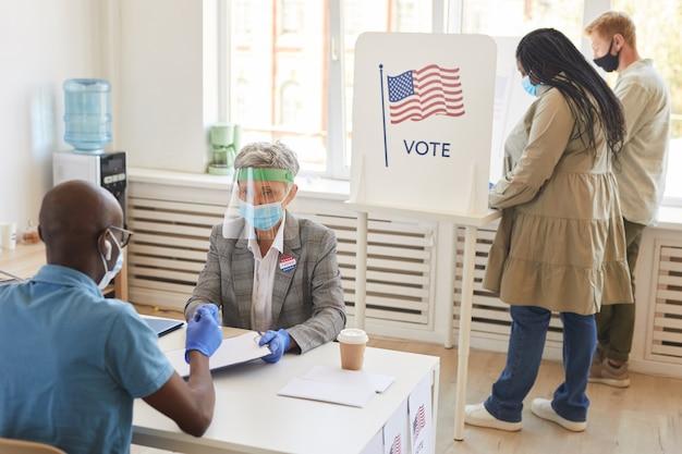 Multi-etnische groep mensen die maskers dragen en ppe-stemmen in het stembureau op de verkiezingsdag na de pandemie, kopie ruimte