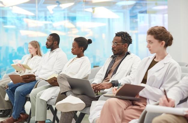 Multi-etnische groep mensen met laboratoriumjassen die in de rij in het publiek zitten tijdens een medisch seminar, kopieer ruimte