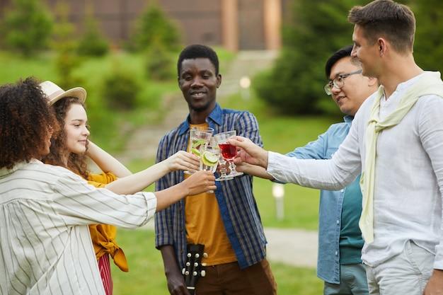 Multi-etnische groep mensen rammelende cocktailglazen en roosteren terwijl u geniet van buitenfeest in de zomer