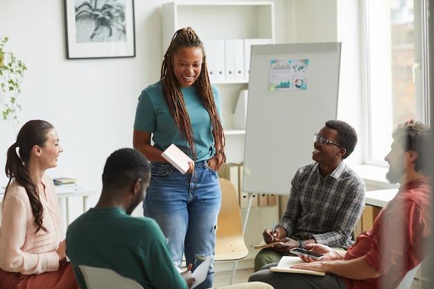 Multi-etnische groep mensen zitten in de cirkel tijdens de bespreking van zakelijk project in kantoor, focus op lachende afro-amerikaanse vrouw in gesprek met collega's