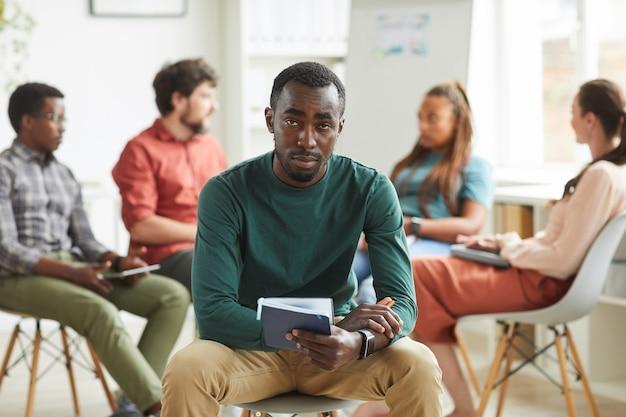 Multi-etnische groep mensen zitten in een cirkel tijdens het bespreken van zakelijk project in kantoor