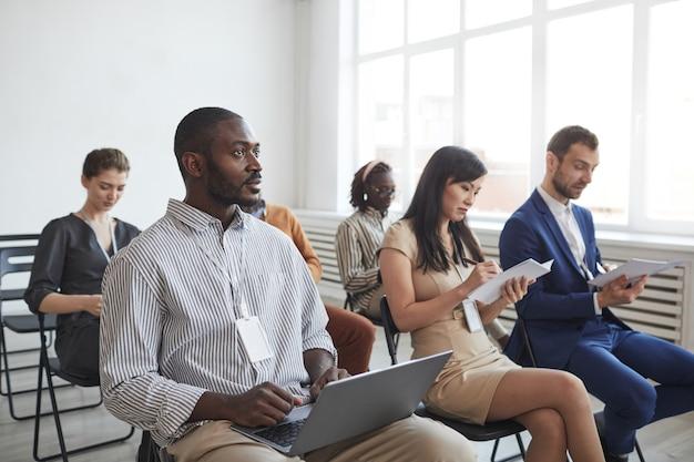 Multi-etnische groep mensen zittend op stoelen in publiek tijdens zakelijke conferentie of seminar en het maken van aantekeningen, kopieer ruimte