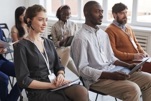 Multi-etnische groep mensen zittend op stoelen in publiek tijdens zakelijke conferentie of seminar, focus op jonge vrouw met headset op voorgrond