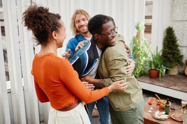 Multi-etnische groep moderne jonge vrienden die elkaar begroeten op een feestje op het dak, kopieer ruimte