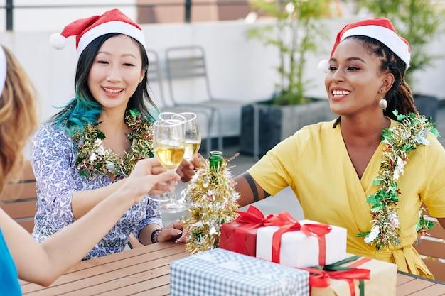 Multi-etnische groep mooie jonge vrouwen in santa claus-hoeden die champagne drinken en cadeautjes uitwisselen op kerstfeest