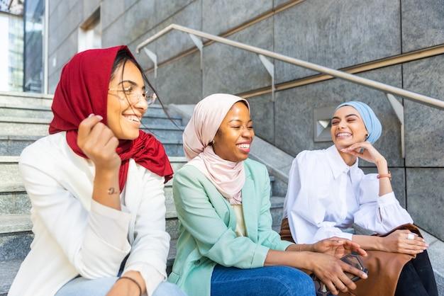 Multi-etnische groep moslimmeisjes die vrijetijdskleding en traditionele hijab-binding dragen en buiten plezier hebben - 3 arabische jonge meisjes