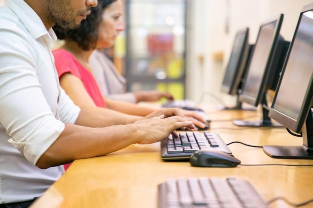 Multi-etnische groep studenten die in computerklasse werken