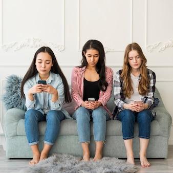 Multi-etnische groep tieners die het gebruiken van telefoons zitten