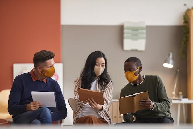 Multi-etnische groep van drie bedrijfsmensen die gezichtsmaskers dragen tijdens het bespreken van project in kantoor