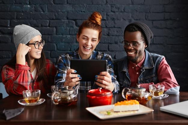 Multi-etnische groep van drie jonge mensen die genieten van online communicatie