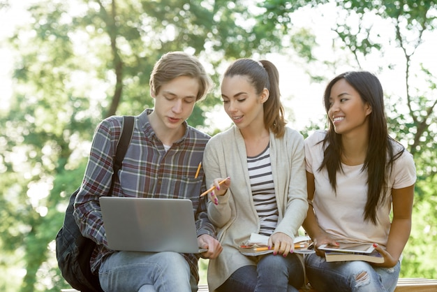 Multi-etnische groep van jonge lachende studenten met behulp van laptopcomputer