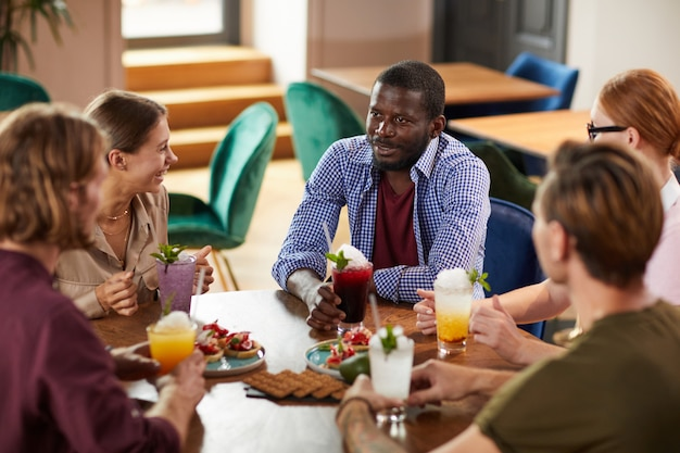 Multi-etnische groep van jonge mensen tijdens de lunch