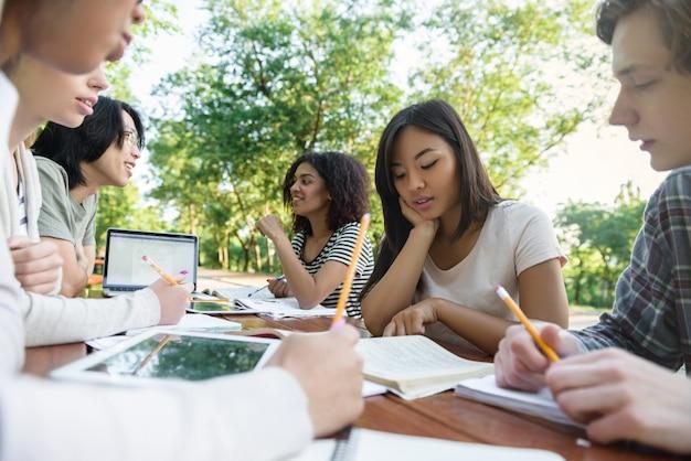 Multi-etnische groep van jonge studenten zitten en studeren