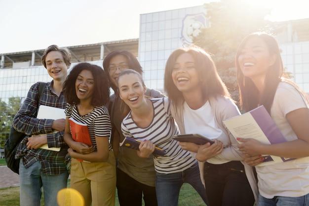 Multi-etnische groep van jonge vrolijke studenten permanent buitenshuis
