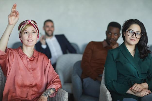 Multi-etnische groep van jonge zakenmensen zitten in auditoruium tijdens opleidingsseminarie, focus op jonge vrouw hand opsteken op de eerste rij, kopie ruimte