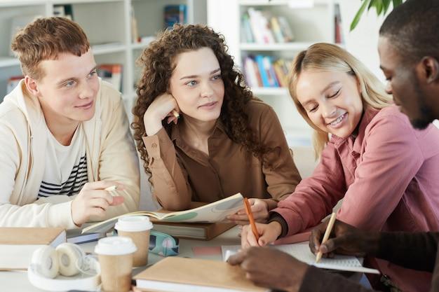Multi-etnische groep van lachende jonge mensen studeren samen zittend aan tafel in de universiteitsbibliotheek en werken aan groepsproject