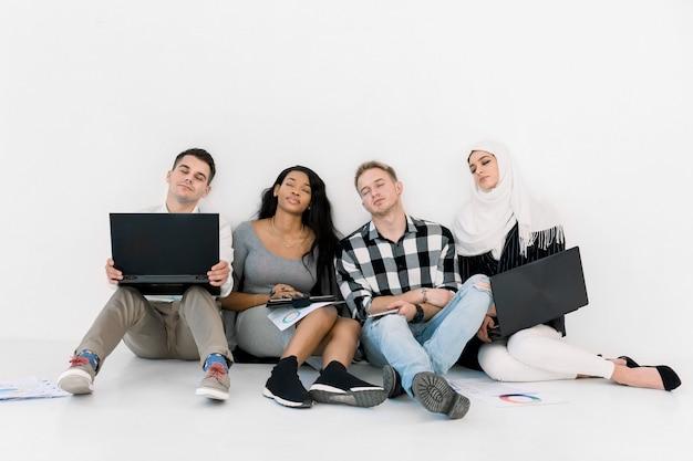 Multi-etnische groep van vier vermoeide studenten of collega's in slaap vallen na hard studeren of werken