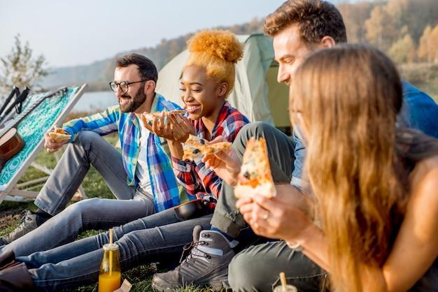 Multi-etnische groep vrienden die nonchalant gekleed zijn en plezier hebben met het eten van pizza tijdens de openluchtrecreatie op de camping