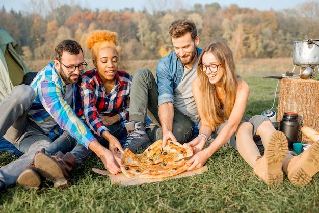 Multi-etnische groep vrienden die nonchalant gekleed zijn en plezier hebben met het eten van pizza tijdens de openluchtrecreatie