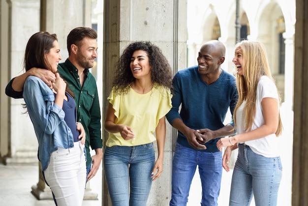Multi-etnische groep vrienden die plezier samen hebben in stedelijke backg