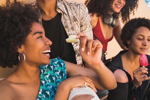 Multi-etnische groep vrienden die van de zomer genieten tijdens het eten van ijs