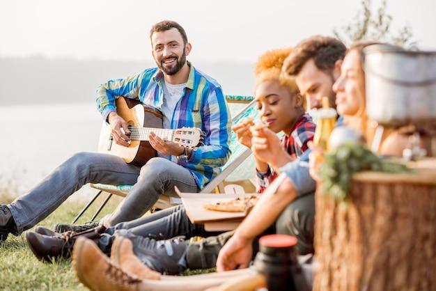 Multi-etnische groep vrienden gekleed terloops picknicken, gitaar spelen en pizza eten, tijdens de openluchtrecreatie bij het meer