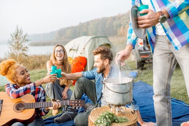 Multi-etnische groep vrienden gekleed terloops rammelende glazen tijdens het diner buiten op de camping
