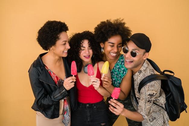 Multi-etnische groep vrienden genieten van de zomer tijdens het eten van ijs.