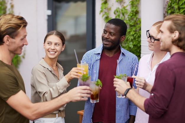 Multi-etnische groep vrienden genieten van drankjes op feestje