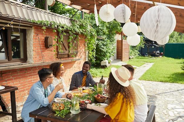 Multi-etnische groep vrienden genieten van een diner samen buiten zittend aan tafel op een open terras