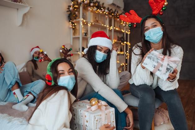 Multi-etnische groep vrienden in santa hoeden glimlachen en poseren voor de camera met geschenken in handen. het concept van het vieren van nieuwjaar en kerstmis onder coronavirusbeperkingen. vakantie in quarantaine