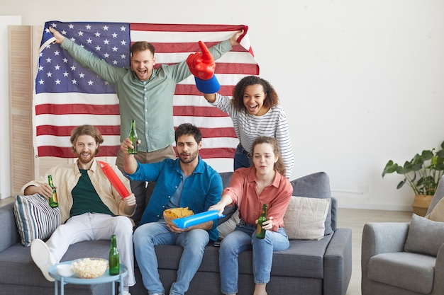 Multi-etnische groep vrienden kijken naar sportwedstrijd en emotioneel juichen terwijl ze de amerikaanse vlag vasthouden