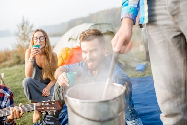 Multi-etnische groep vrienden nonchalant gekleed met een smakelijk diner met soep gekookt in een ketel tijdens de picknick op de camping