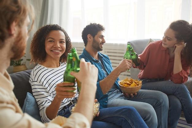 Multi-etnische groep vrienden rammelende bierflesjes tijdens het kijken naar tv samen zittend op een comfortabele bank thuis, focus op lachende afro-amerikaanse vrouw op voorgrond