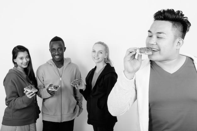 Multi-etnische groep vrienden samen als diversiteitsconcept tegen witte muur in zwart-wit
