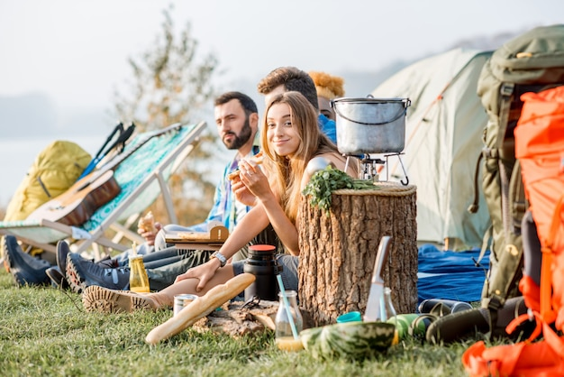 Multi-etnische groep vrienden terloops gekleed met een picknick, pizza eten, tijdens de openluchtrecreatie met tent en wandeluitrusting in de buurt van het meer
