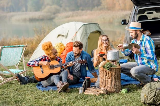 Multi-etnische groep vrienden terloops gekleed met een picknick, soep koken met ketel, gitaar spelen tijdens de openluchtrecreatie in de buurt van het meer