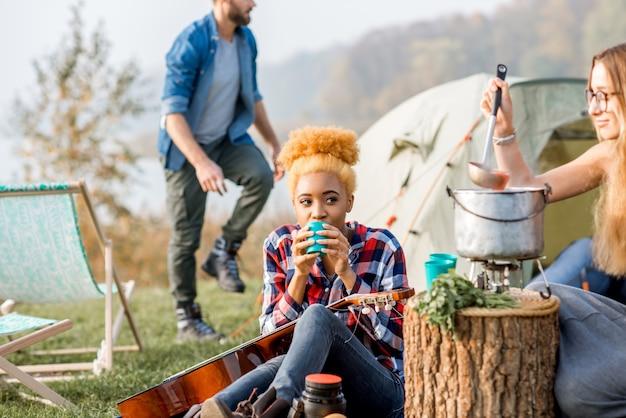 Multi-etnische groep vrienden terloops gekleed met een picknick, soep koken met ketel tijdens de openluchtrecreatie in de buurt van het meer