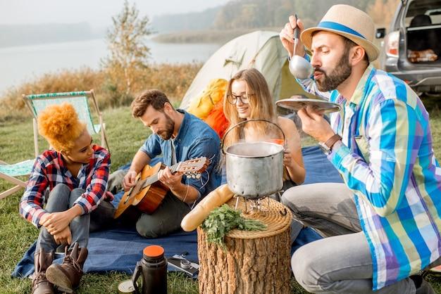 Multi-etnische groep vrienden terloops gekleed met een picknick, soep koken met ketel tijdens de openluchtrecreatie met tent, auto en wandeluitrusting in de buurt van het meer