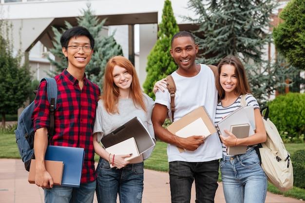 Multi-etnische groep vrolijke jonge studenten die buiten samen staan