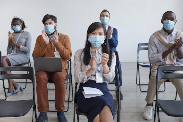 Multi-etnische groep zakenmensen die maskers dragen en applaudisseren met sociale afstand terwijl ze op stoelen in het publiek zitten tijdens een zakelijke conferentie of seminar