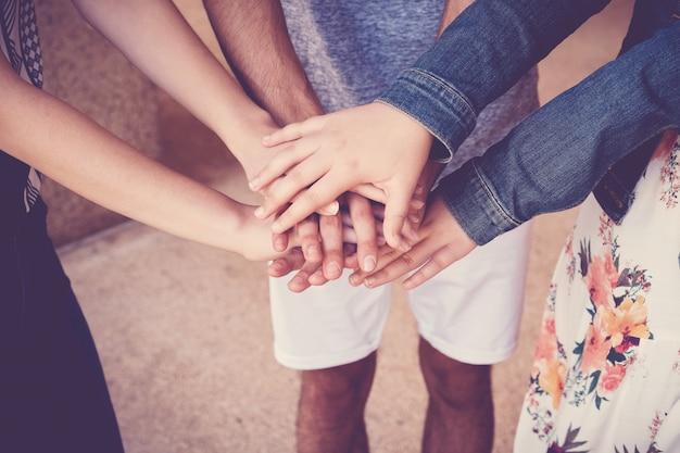 Multi-etnische handen van jonge volwassenenstudenten die handen, vrijwilligers en liefdadigheidsgroepswerkconcept samenbrengen