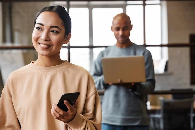 Multi-etnische jonge vrouwelijke en mannelijke collega's die samenwerken op kantoor