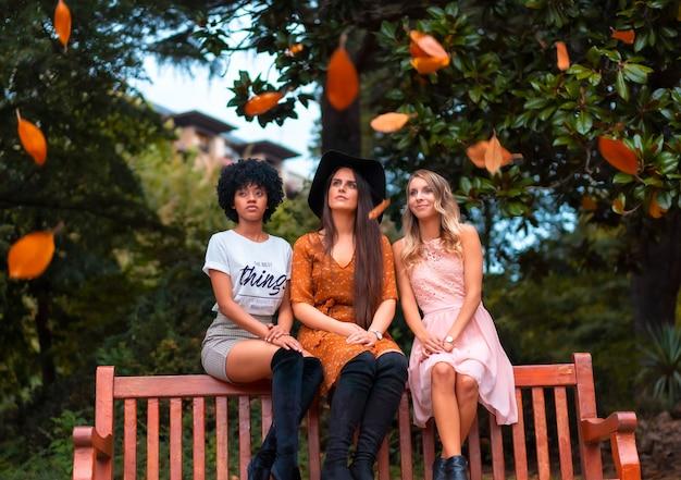 Multi-etnische levensstijl in een bos in de herfst van drie vrienden zittend op een bankje