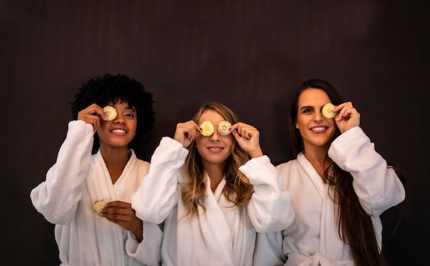 Multi-etnische levensstijl van drie mooie vriendinnen plezier in een schoonheidssalon