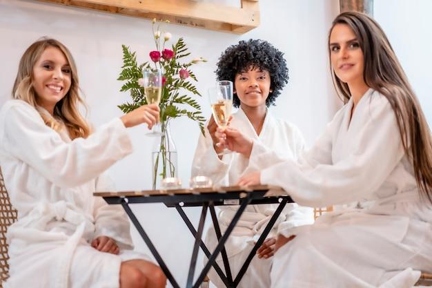 Multi-etnische levensstijl van drie vrienden die champagne drinken in een schoonheidssalon