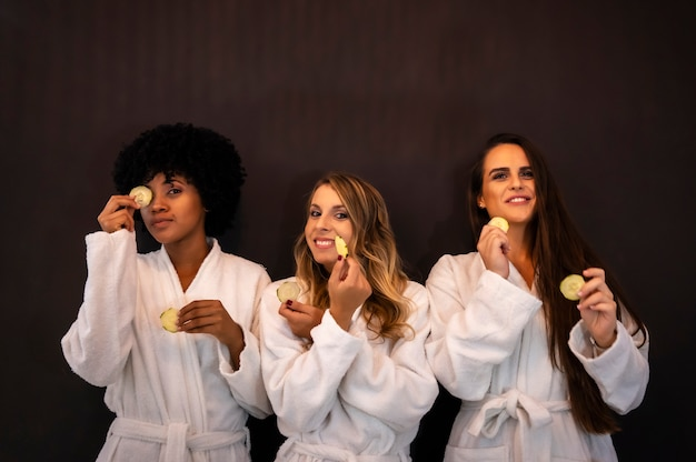 Multi-etnische levensstijl van drie vrienden in een schoonheidssalon, met komkommers in handen