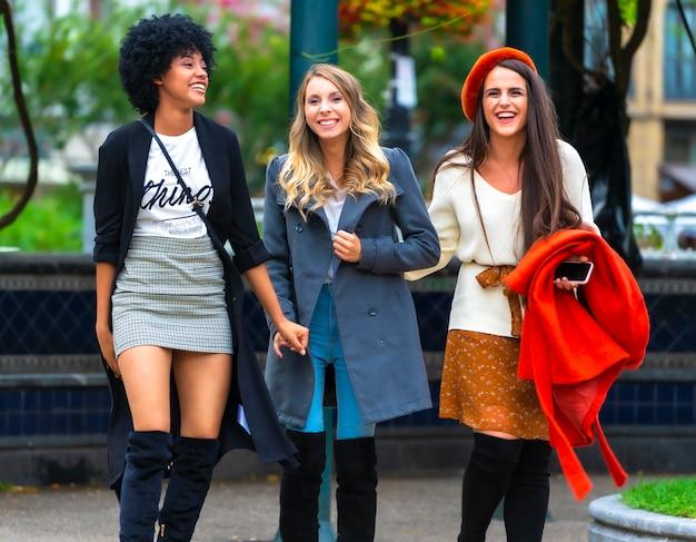 Multi-etnische levensstijl van drie vriendinnen die plezier hebben in de stad