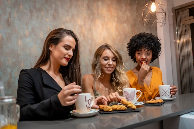 Multi-etnische levensstijl van drie vriendinnen met koffie en koekjes in een koffieshop